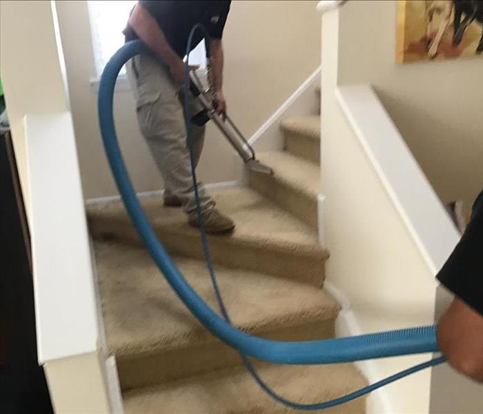 Interior carpeted staircase with SERVPRO Technician cleaning the carpet.