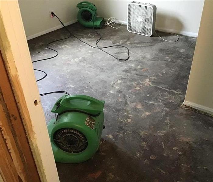 Bedroom with carpeting pulled and SERVPRO drying equipment in the room.