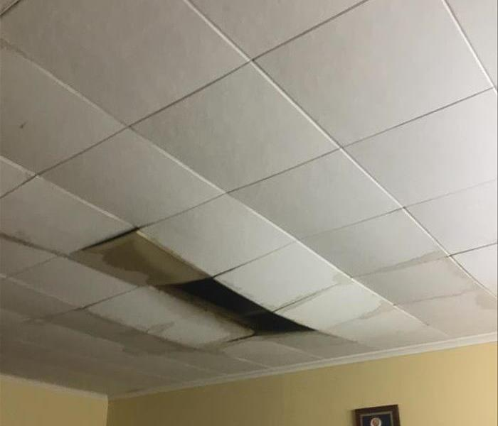 Dirty and falling ceiling tiles after a house fire.