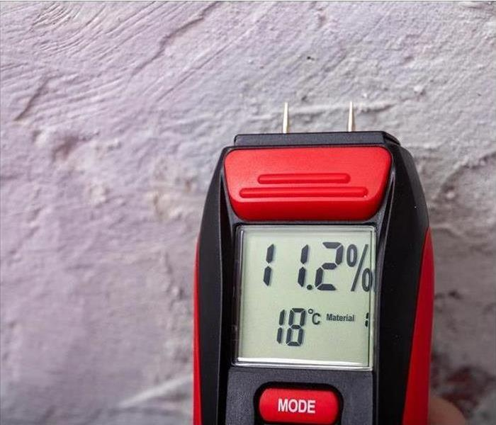 red moisture meter by a stucco wall