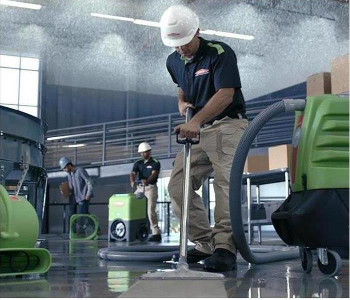 SERVPRO Technician extracting water in a warehouse.