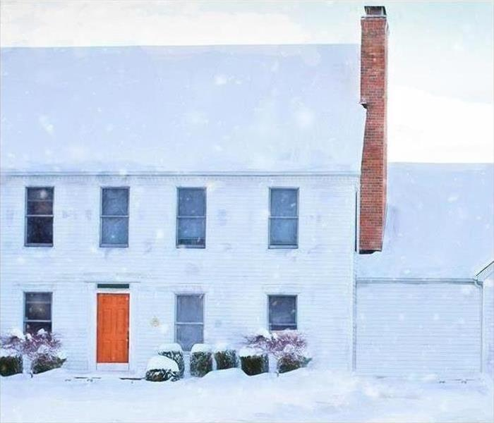 white brick home with snow covering the roof and ground