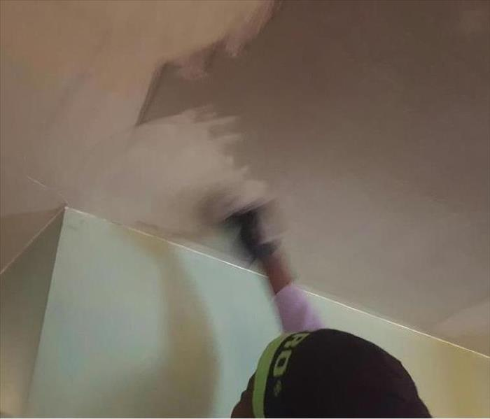 SERVPRO Technician cleaning soot off a ceiling.