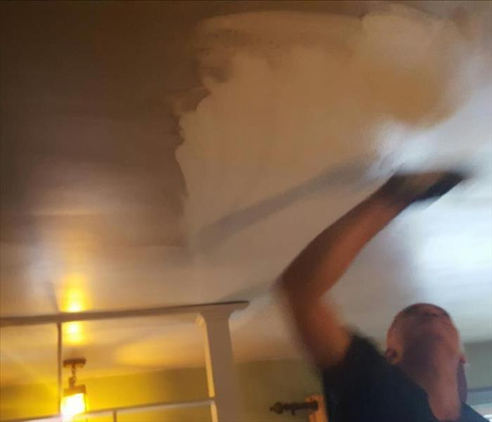 SERVPRO Technicians cleaning fire damaged ceiling in a home.
