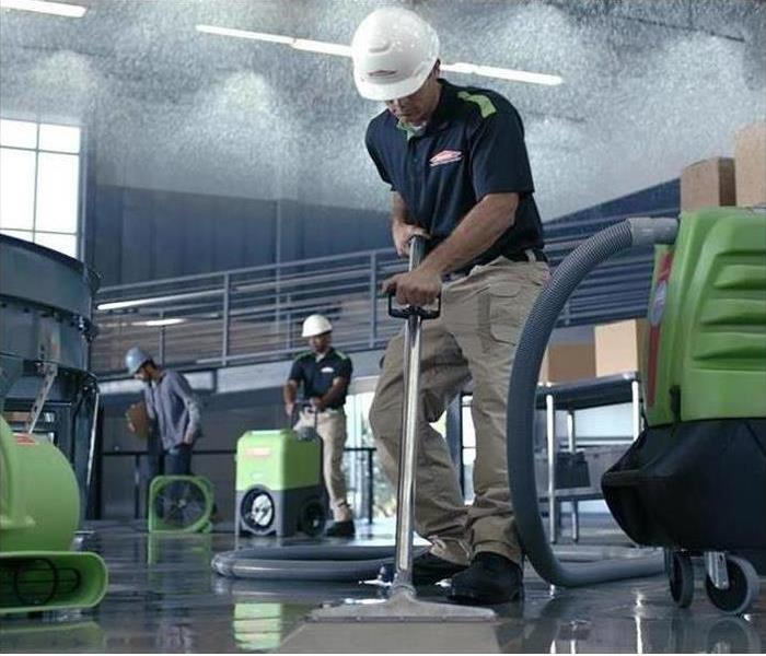 SERVPRO Technicians Cleaning Water Damage in a warehouse
